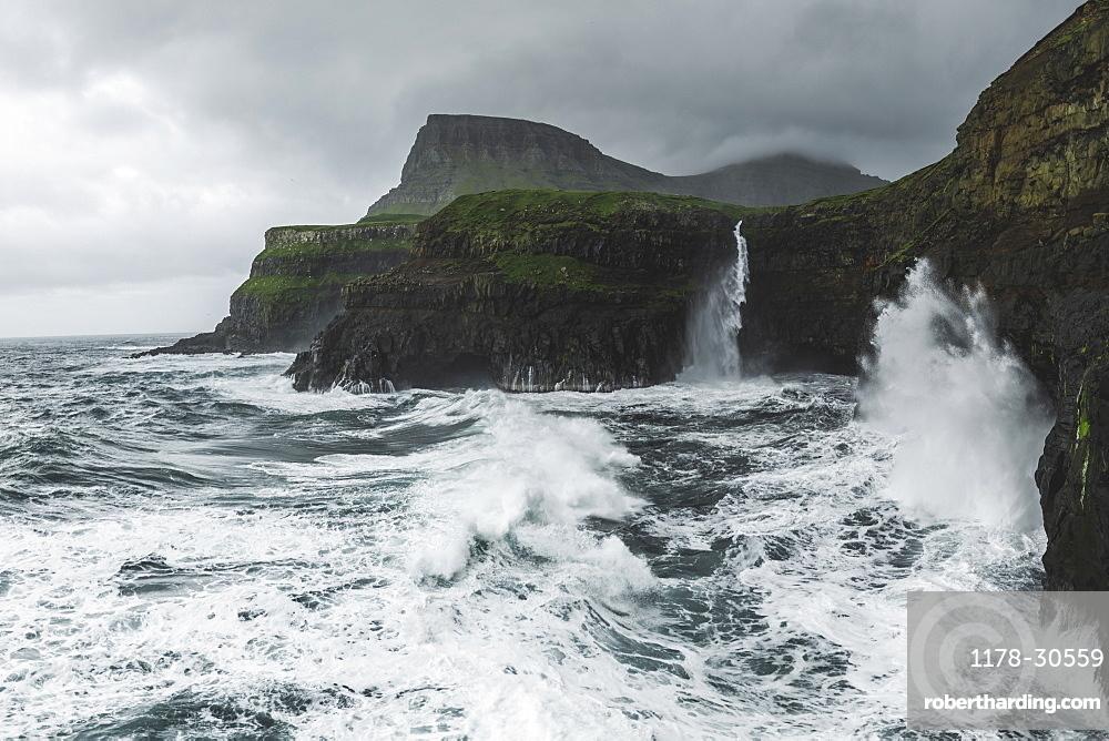Denmark, Faroe Islands, Gasadalur Village, Mulafossur Waterfalll, Coastline with Mulafossur Waterfall falling into Atlantic Ocean in stormy day