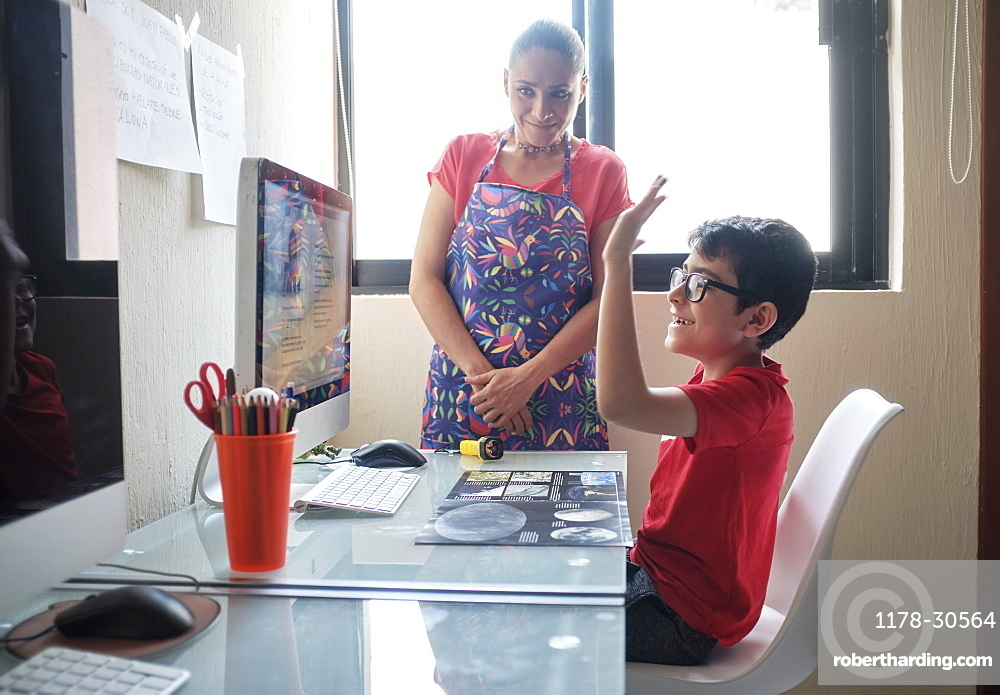 Mother watching son (8-9) during e-learning at home due to Covid-19 lockdown