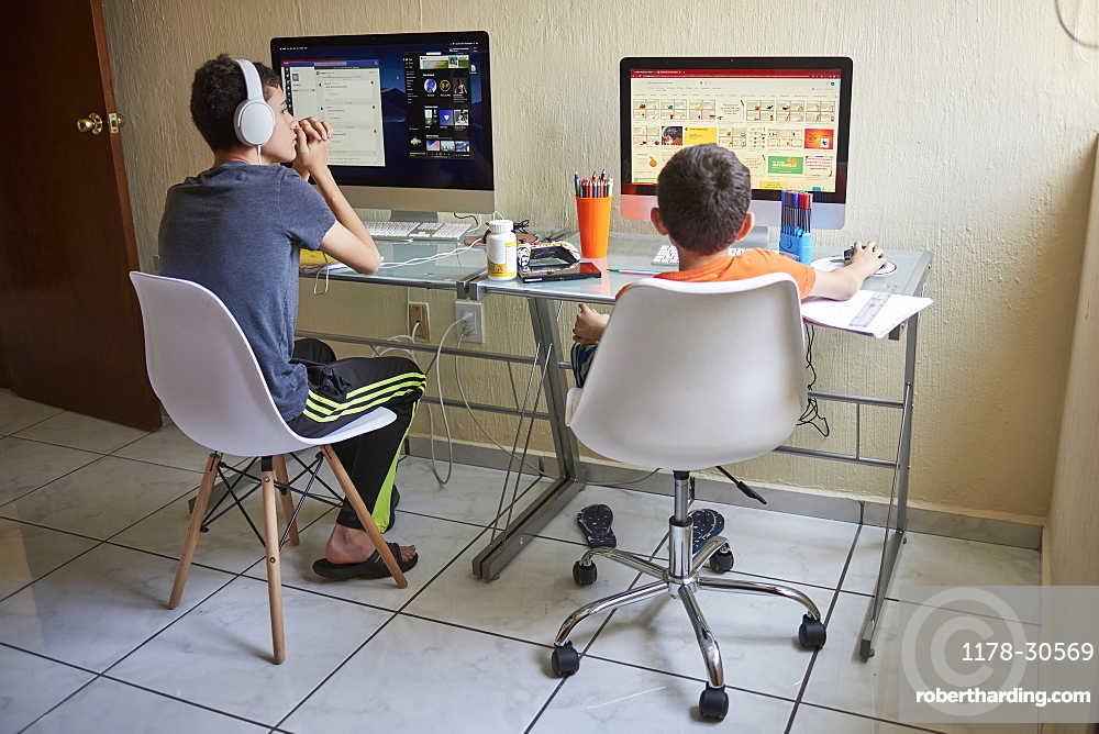 Two boys (8-9, 14-15) e-learning at home during Covid-19 lockdown