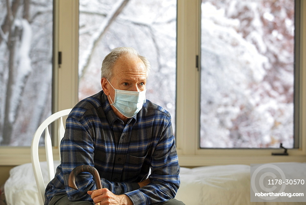 Senior man in Covid protective mask sitting on chair by window and holding cane