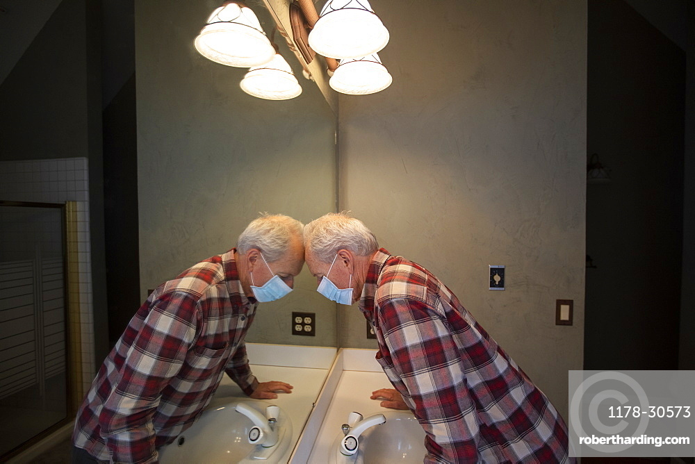 Senior man in Covid protective mask leaning head on mirror in bathroom