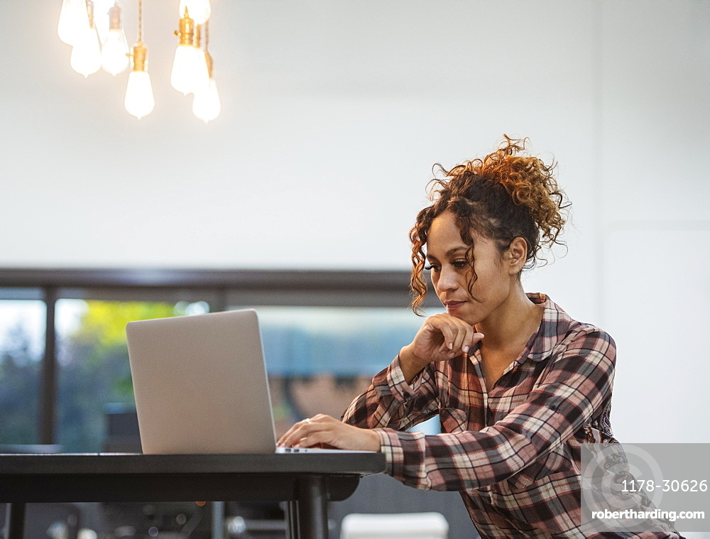 Woman sitting using laptop in office
