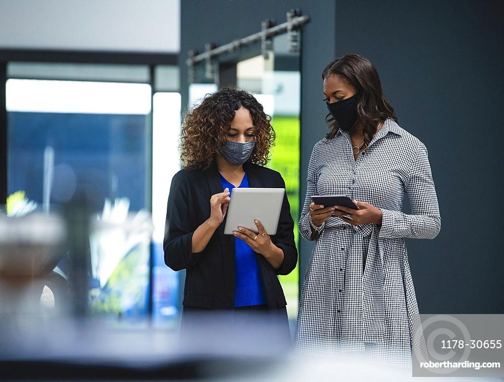 Businesswomen in face masks using digital tablets in office