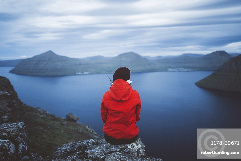 Denmark, Faroe Islands, Klaksvik, Woman sitting on edge of cliff over sea and looking at view