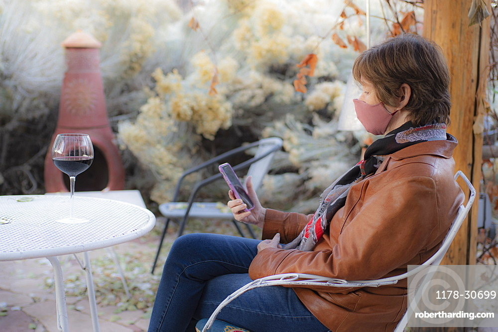 Woman wearing protective face mask sitting on bench