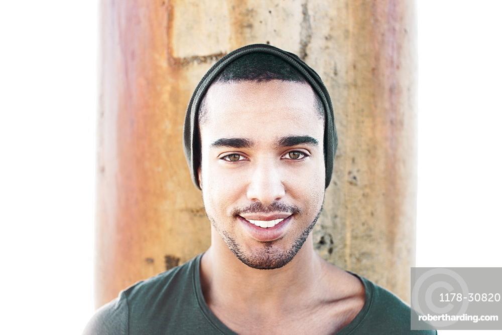 Smiling Hispanic man wearing cap