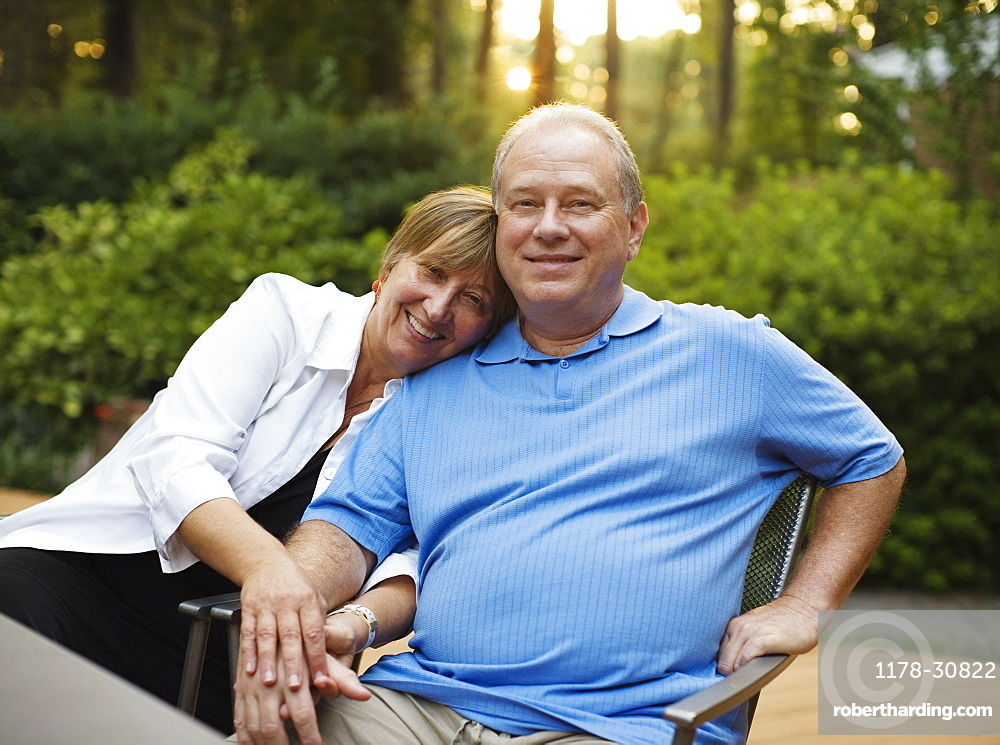Caucasian couple sitting together and holding hands