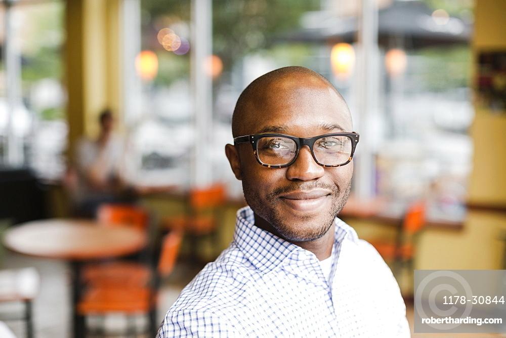 Black man smiling in coffee shop