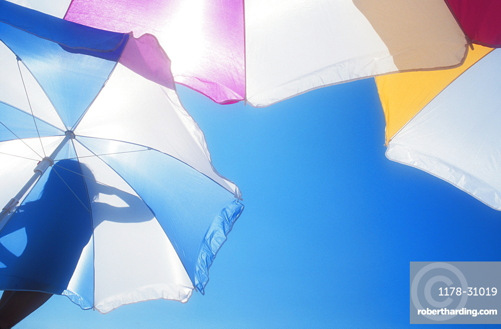 Low angle view of silhouette of woman on beach umbrella against blue sky