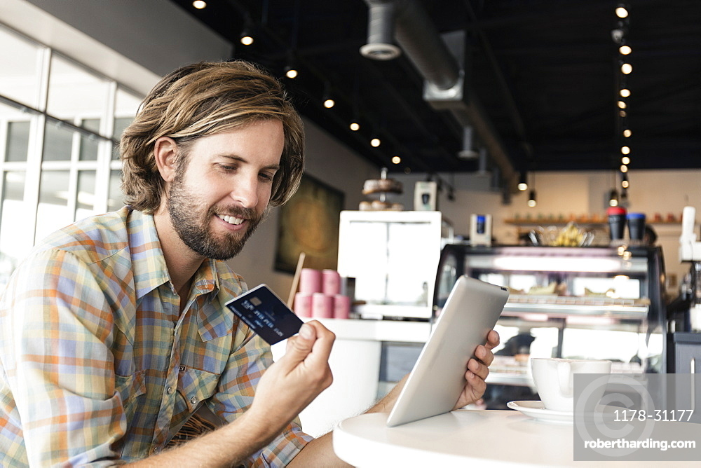 Mid adult man in coffee shop, using digital tablet, holding credit card