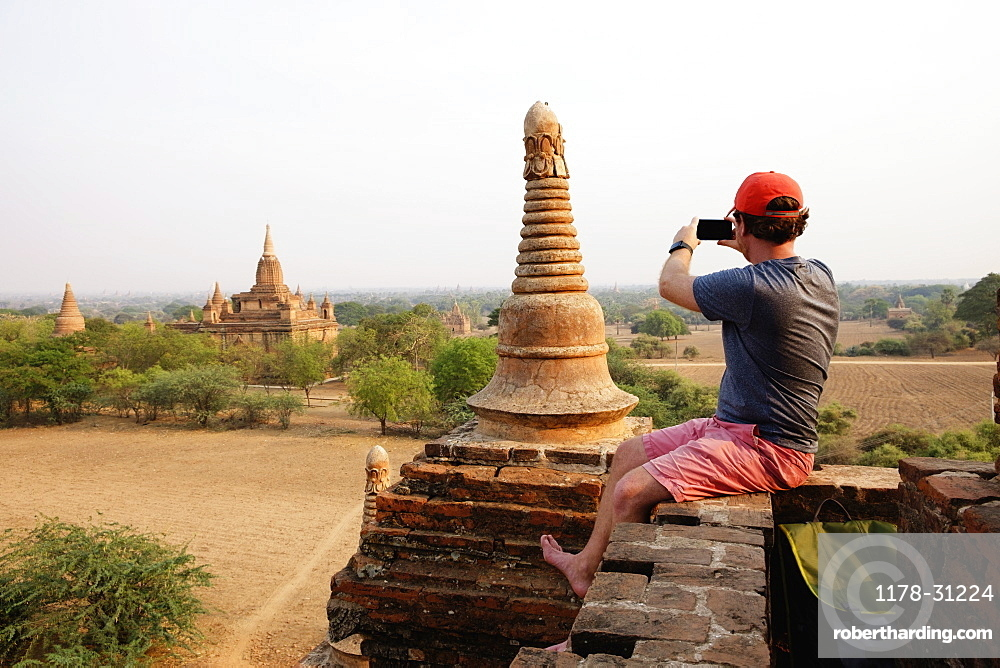 Man taking photograph from stone wall, Bagan Archaeological Zone, Buddhist temples, Mandalay, Myanmar