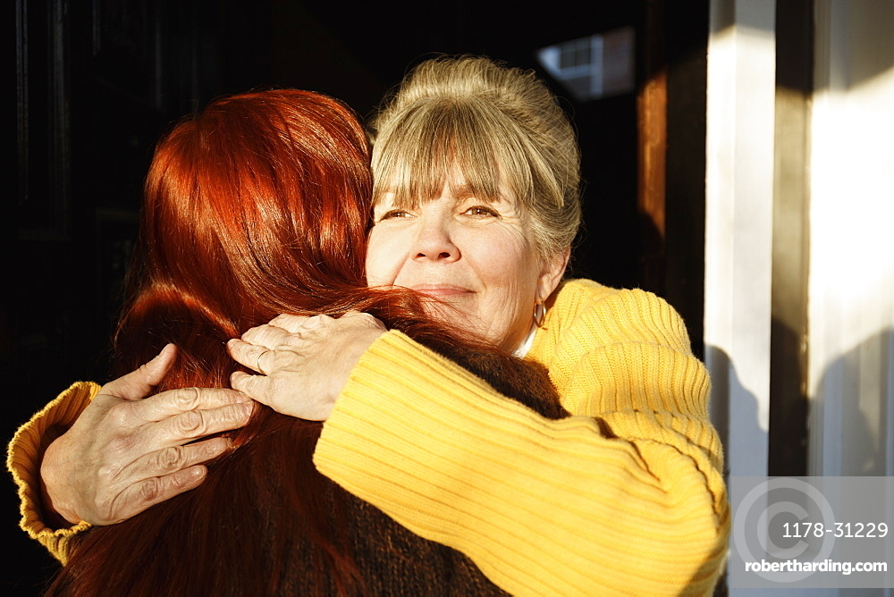 Rear view of senior woman and adult daughter hugging at front door