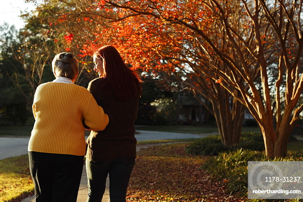 Rear view of senior woman and adult daughter strolling in suburban park