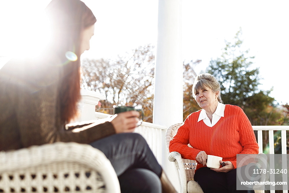 Senior woman and adult daughter drinking coffee on porch