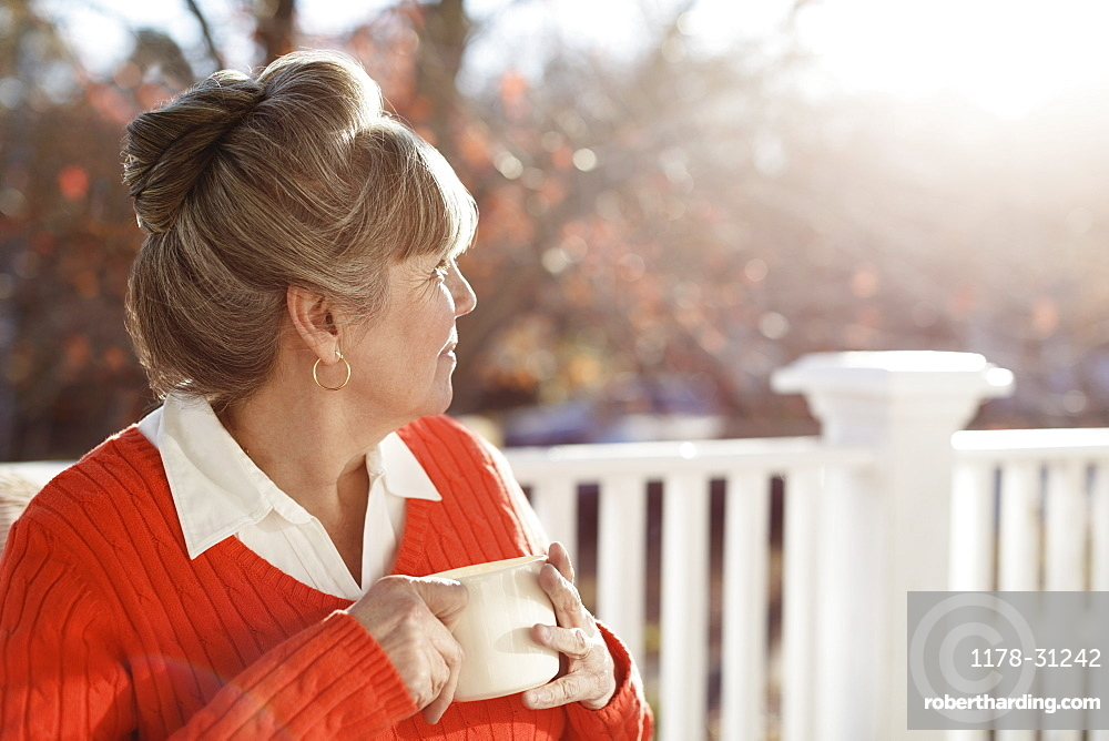 Senior woman drinking coffee and looking over shoulder from porch