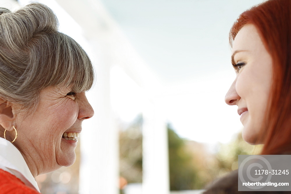 Close up of senior woman and adult daughter laughing on porch
