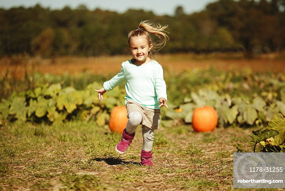 Girl running in pumpkin field