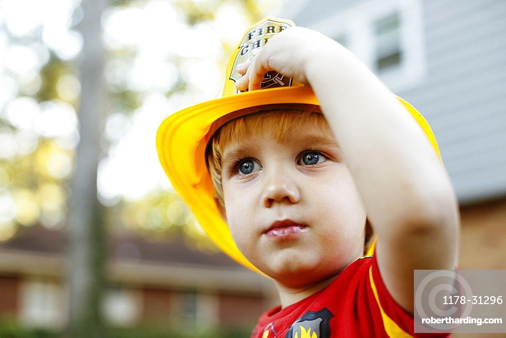 Young boy wearing fireman's helmet