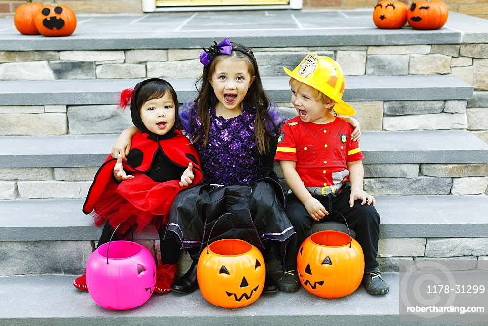 Three children sitting on steps with trick or treat buckets