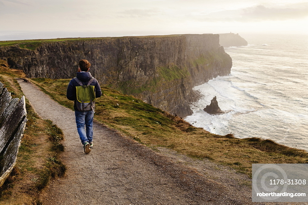 Mid adult man walking on The Cliffs of Moher, The Burren, County Clare, Ireland