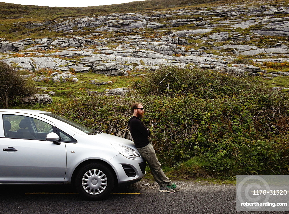 Mid adult man leaning against car bonnet