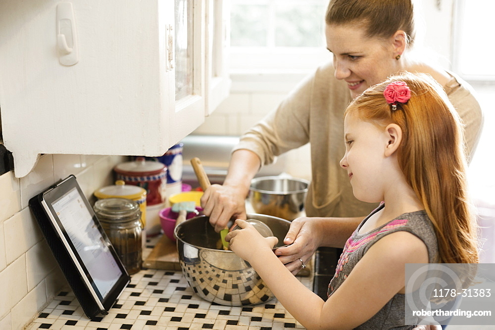 Girl and mother looking at recipe on digital tablet in kitchen