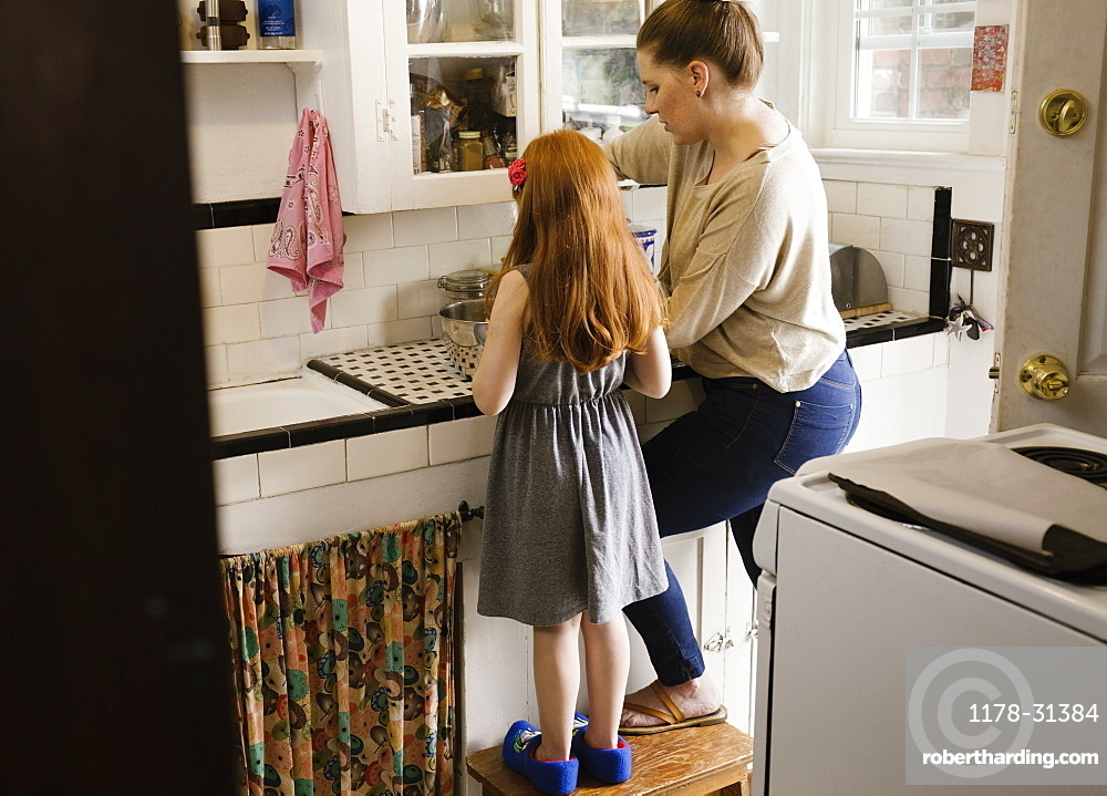 Girl and mother baking together in kitchen