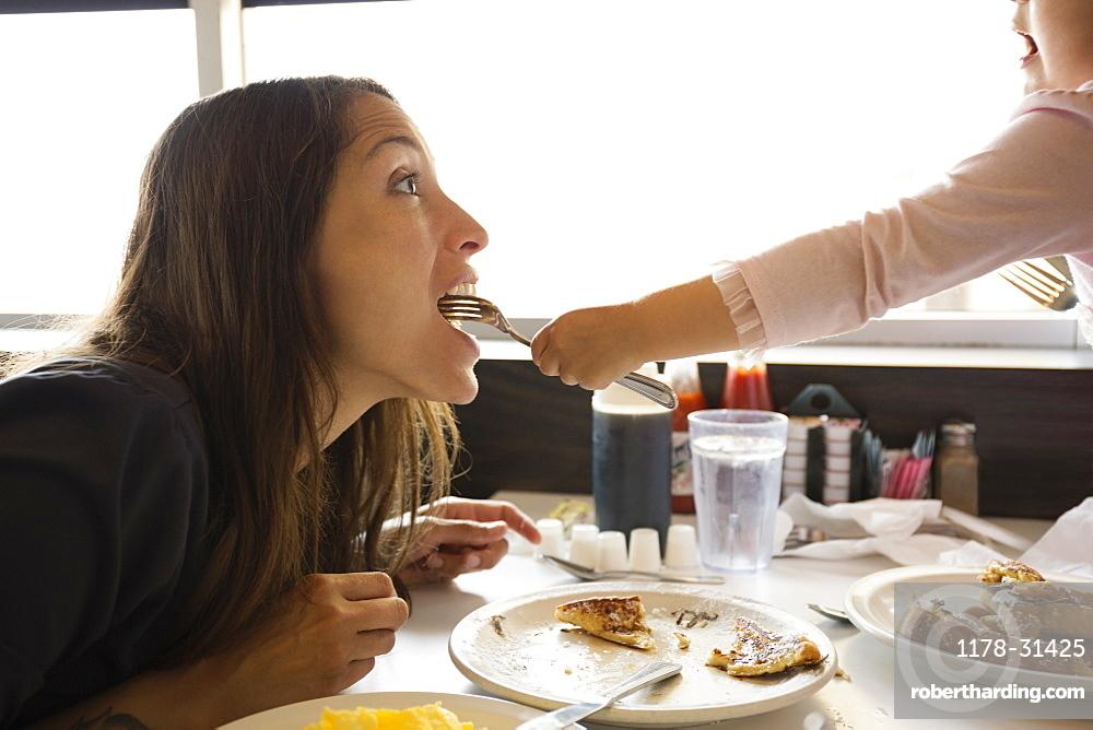 Toddler daughter feeding mother from fork in diner