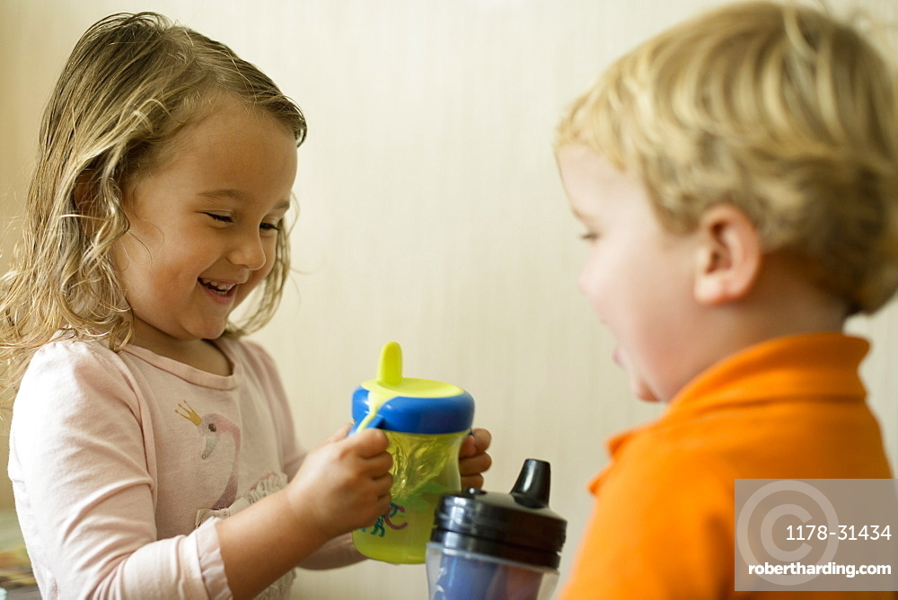 Male and female toddler friends having a drink