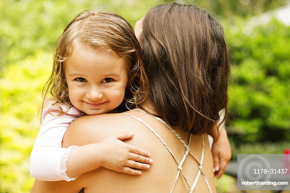 Portrait of female toddler carried by mother in garden