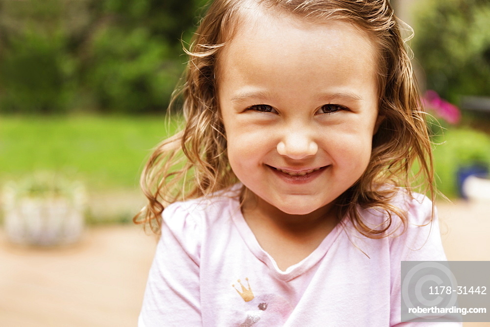 Close up portrait of smiling female toddler in garden