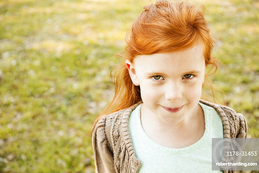 Portrait of red haired girl in park