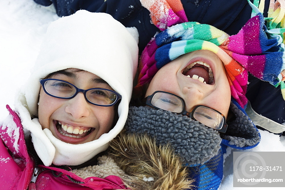 Boy and girl wearing winter hats and glasses, laughing