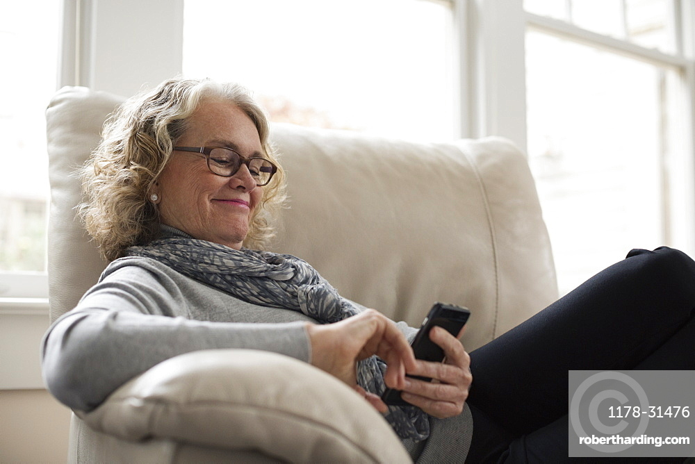 Senior woman relaxing on chair with mobile phone