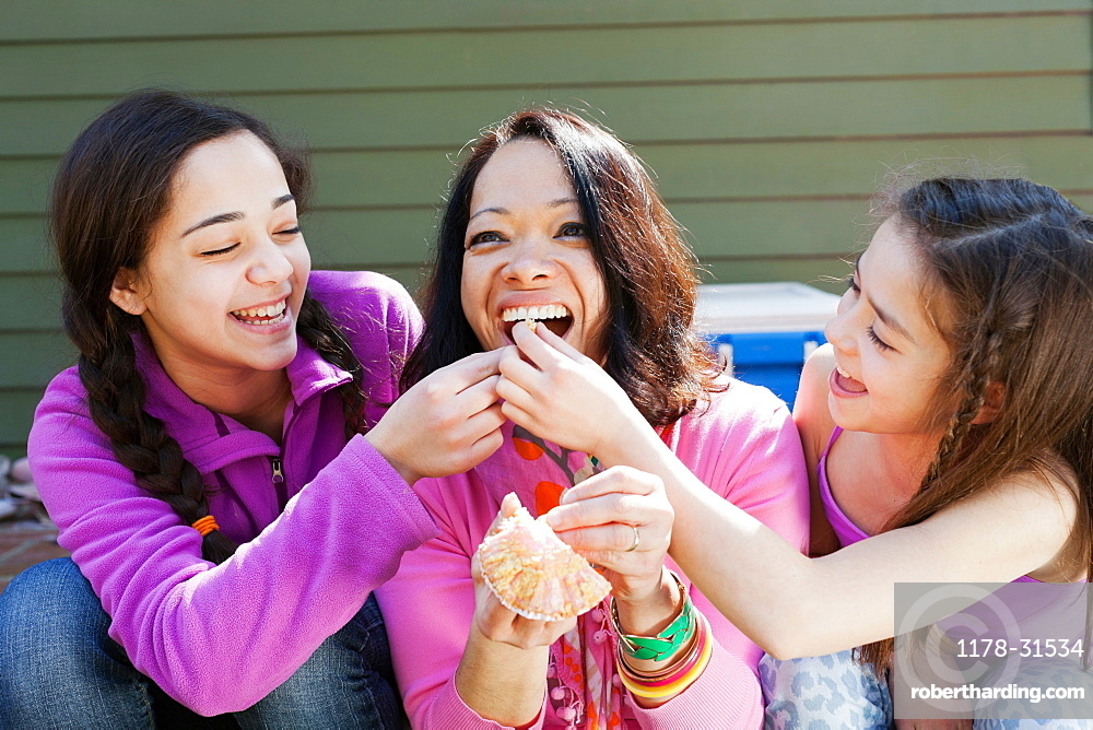 Two sisters feeding mother cupcake