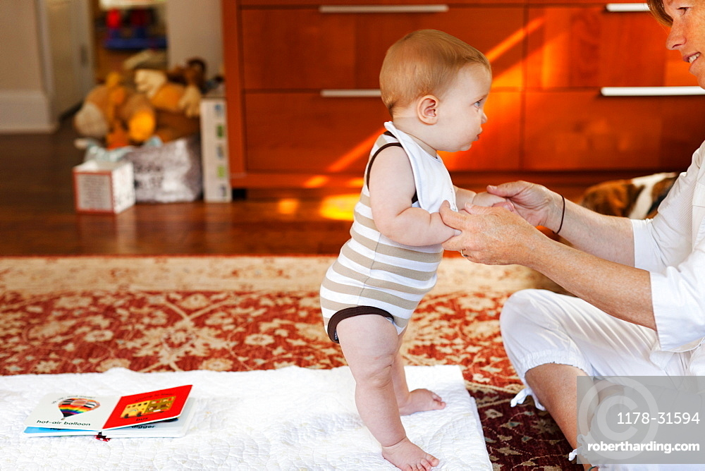 Mother and baby son playing on carpet
