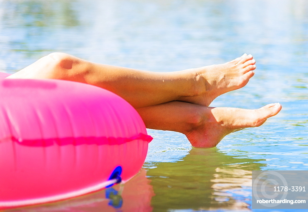 Cropped shot of legs of young woman floating on pink swim ring
