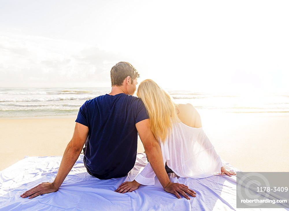 Rear view of young couple sitting on blanket on sandy beach, looking at sea, Jupiter, Florida