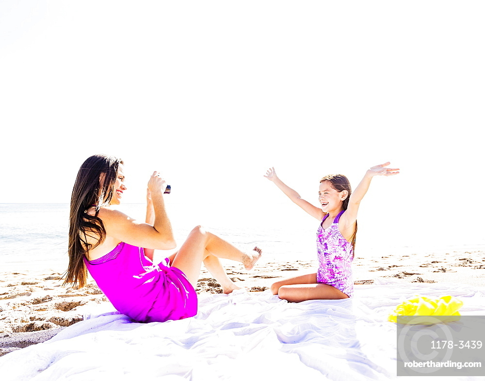 Mom taking picture of her daughter (6-7) on beach, Jupiter, Florida