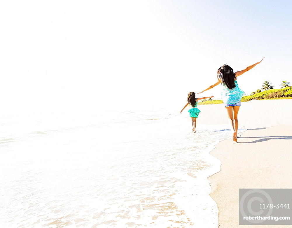 Rear view of girl (6-7) and her mom running on beach, Jupiter, Florida