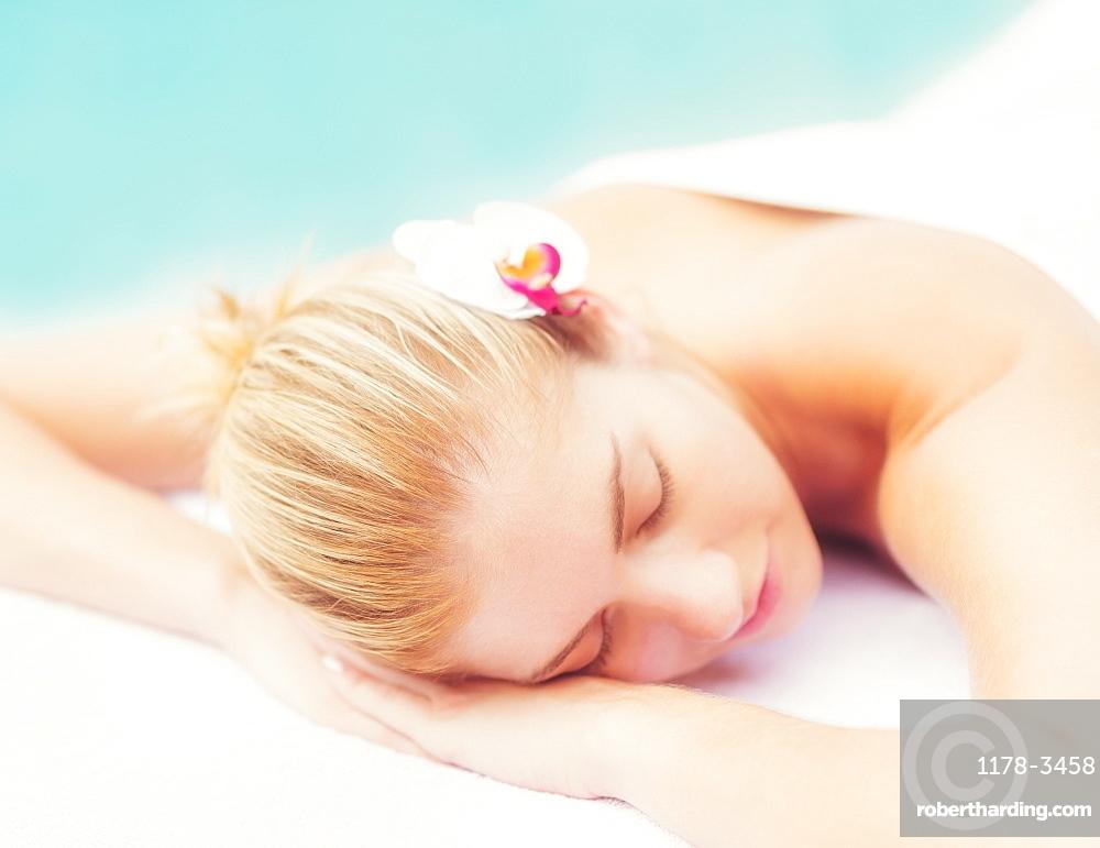 Woman lying next to swimming pool