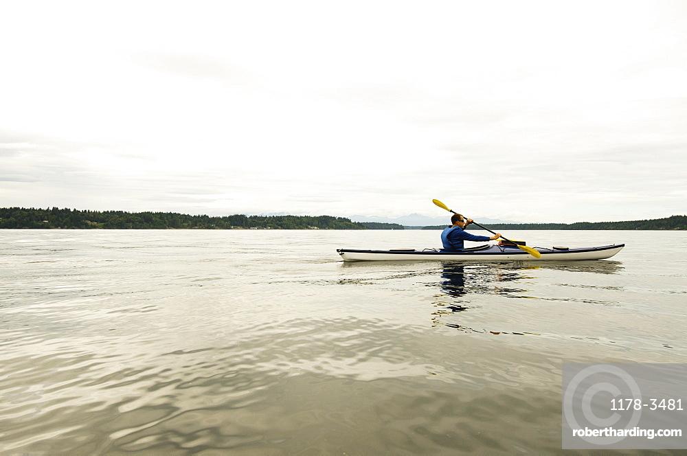 Man kayaking on lake, Olympia, Washington, USA