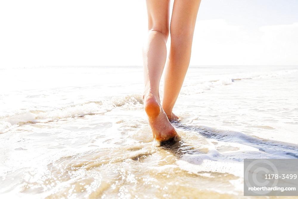 Legs of woman walking in sea