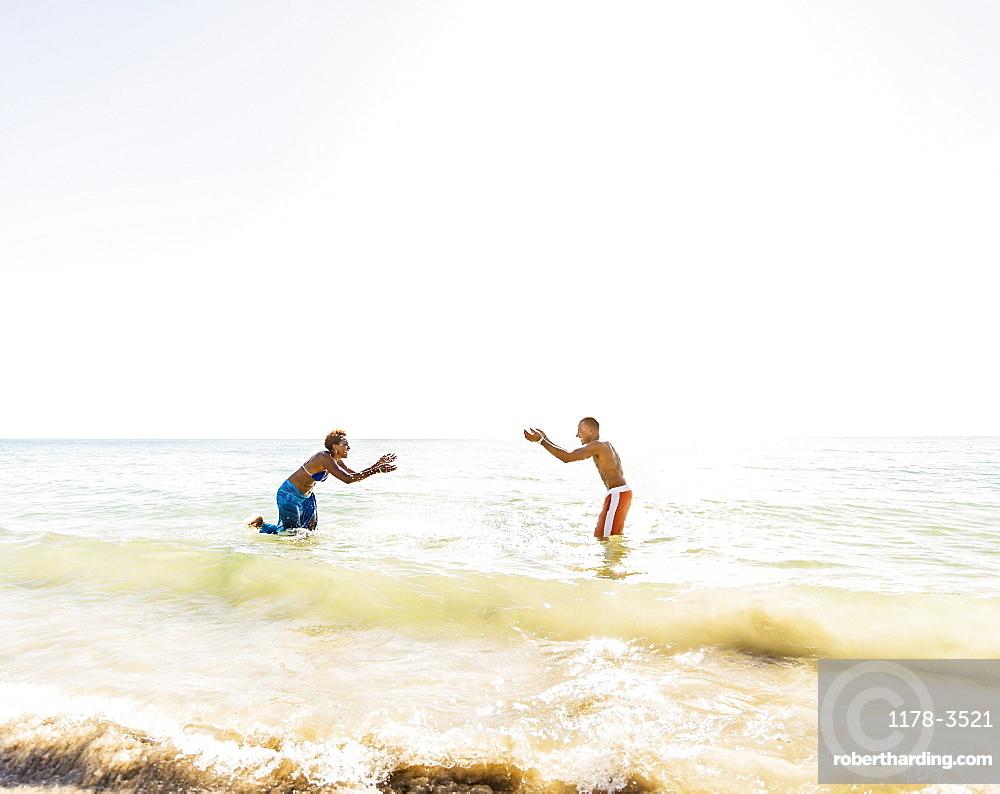 Man and woman splashing water on beach