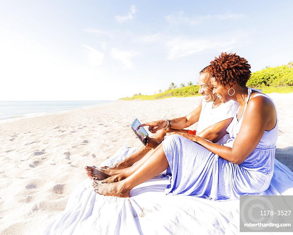 Man and woman sitting on beach, Jupiter, Florida