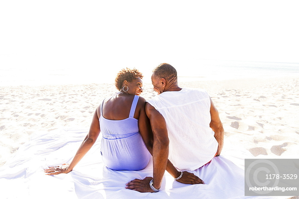 Man and woman sitting on beach