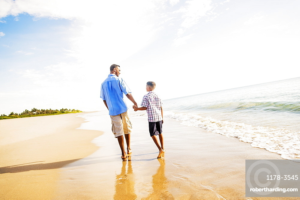 Father and son (10-11) walking on beach, Jupiter, Florida