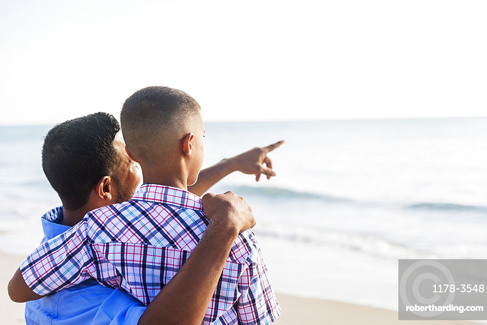 Father and son (10-11) embracing on beach