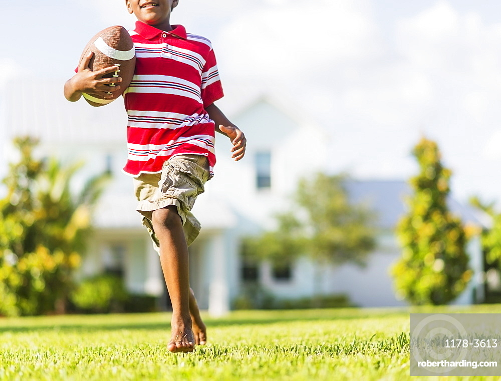 boy (6-7) playing football, Jupiter, Florida