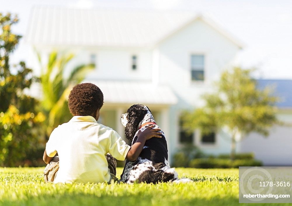 Back view of boy (6-7) sitting with dog, Jupiter, Florida